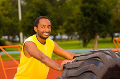 Man wearing yellow shirt and blue shorts lifting large tractor tire during strength excercise, outdoors training Stock Photos