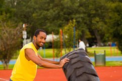 Man wearing yellow shirt and blue shorts lifting large tractor tire during strength excercise, outdoors training Royalty Free Stock Photography