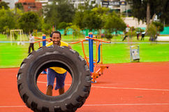 Man wearing yellow shirt and blue shorts lifting large tractor tire during strength excercise, outdoors training Stock Image