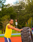 Man wearing yellow shirt and blue shorts lifting large tractor tire during strength excercise, outdoors training Stock Images