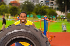 Man wearing yellow shirt and blue shorts lifting large tractor tire during strength excercise, outdoors training Royalty Free Stock Photo