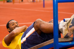 Man wearing yellow shirt and blue shorts lying down on wooden training plank doing situps smiling, orange athletic Stock Photo