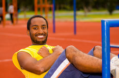 Man wearing yellow shirt and blue shorts lying down on wooden training plank doing situps smiling, orange athletic Royalty Free Stock Photography