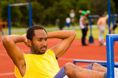 Man wearing yellow shirt and blue shorts lying down on wooden training plank doing situps smiling, orange athletic. Surface background Stock Photography