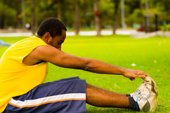 Man wearing yellow shirt and blue shorts sitting down on green grass stretching by touching shoes with hands, training. Concept Royalty Free Stock Photography