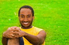 Man wearing yellow shirt and blue shorts sitting on green grass, holding arm around knee smiling to camera, training Royalty Free Stock Image