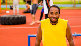 Man wearing yellow shirt and blue shorts smiling while posing for camera at outdoors training facility with orange Stock Photo