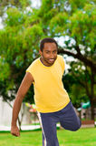 Man wearing yellow shirt and blue shorts stretching legs using hands in park sorrounded by green grass trees, training Royalty Free Stock Images