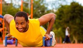 Man wearing yellow shirt doing push-ups at outdoors training facility, orange athletic surface and green trees Stock Photo
