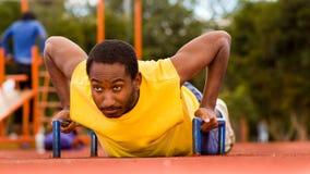 Man wearing yellow shirt doing push-ups at outdoors training facility, orange athletic surface and green trees Royalty Free Stock Image