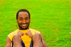 Man wearing yellow shirt doing situps in park sorrounded by green grass and trees, happy facial expression, training Stock Photography