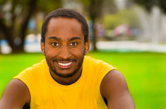 Man wearing yellow shirt sitting in park sorrounded by green grass and trees, happy facial expression, training concept Stock Image