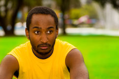Man wearing yellow shirt sitting in park sorrounded by green grass and trees, serious facial expression, training Royalty Free Stock Images