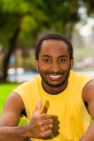 Man wearing yellow shirt sitting in park sorrounded by green grass and trees, serious facial expression, training Stock Photography