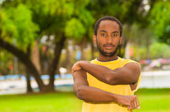 Man wearing yellow shirt stretching arms in park sorrounded by green grass and trees, training concept.  Stock Image