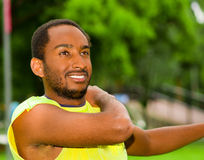 Man wearing yellow shirt stretching arms in park sorrounded by green grass and trees, training concept.  Royalty Free Stock Photos