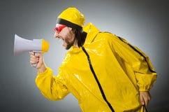 Man wearing yellow suit with loudspeaker Stock Image