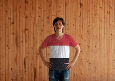 Man wearing Yemen flag color shirt and standing with akimbo on the wooden wall background. A horizontal tricolour of red white and black stock image