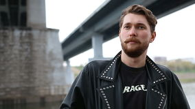 The man wears a black jacket. Bridges in the background stock footage