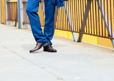 Man wears blue trousers with brown shoes. Standign on bridge Royalty Free Stock Images