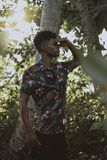 Man Wears Multicolored Floral Button-up Short-sleeved Shirt Beside Tree Stock Images