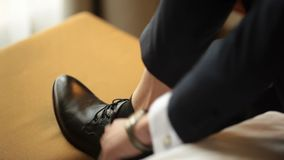 A man wearing black shoes. The man wears shoes. Tie the laces on the shoes. Men`s style. Professions. To prepare for work, to the meeting stock video