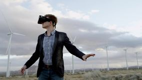 The man wears the virtual headset in the countryside. The man wearing the virtual headset and doing some moves, he is in the countryside with windmills on the stock footage