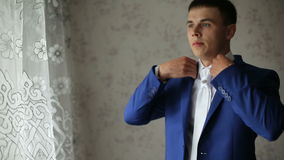 Man wears wedding dress. Young bride dress and shirt buttons.Happy young groom on their wedding day.Young handsome groom wears wedding jacket, standing in front stock video footage