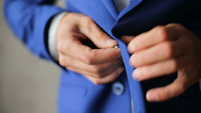 Man wears wedding dress. Young bride dress and shirt buttons.Happy young groom on their wedding day.Young handsome groom wears wedding jacket, standing in front stock video