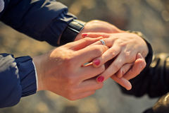 Man wears a wedding ring on woman's hand Royalty Free Stock Photos
