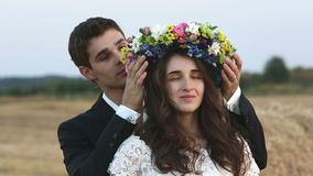 The man wears a wreath of flowers on the head of the girl. Medium shot stock video