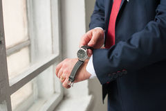 Man wears on wrist watch. The man wears on his wrist watch while standing at the window. A man dressed in a suit, shirt and red tie. Businessman or fiance Stock Image
