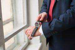 Man wears on wrist watch Stock Image