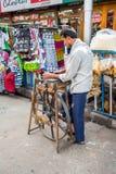 A man weaves thread. A street vendor weaves thread in a side street in Kolkata, India stock photos