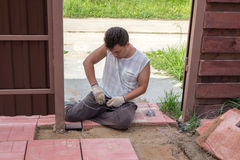 Man weaves wire for laying paving tiles stock images