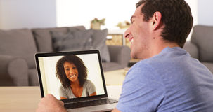Man webcamming with friend on laptop Royalty Free Stock Images