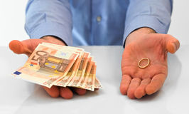 Man with wedding ring and money. Stock Photo