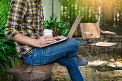 Man on week-end working on laptop computer outdoor in a park gar. Den during a sunny summer day Royalty Free Stock Image