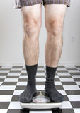 Man weighing himself. Man in underwear and socks standing on a scale Royalty Free Stock Photo