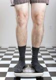 Man weighing himself Royalty Free Stock Photo