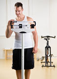 Man weighing himself in health club Royalty Free Stock Photo