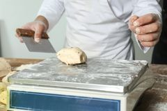 Man weighing raw dough on scale Royalty Free Stock Photo