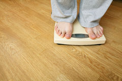 Man on a weighing scale royalty free stock photography
