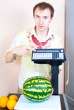 Man weighing watermelon at market royalty free stock image