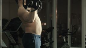The man the weightlifter lifts a bar in a gym stock video