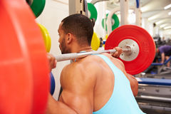 Man weightlifting�barbells at a squat rack in a gym Royalty Free Stock Images