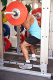 Man weightlifting�barbells at a squat rack in a gym Stock Photography