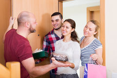 Man welcomes smiling friends Stock Image