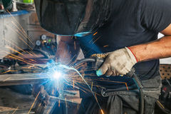 Man weld  a metal  with a  welding machine. A strong man is a welder in a black T-shirt, in a welding mask and welders leathers, a metal product is welded with a Royalty Free Stock Photos
