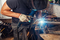 Man weld  a metal  with a  welding machine. A strong man is a welder in a black T-shirt, in a welding mask and welders leathers, a metal product is welded with a Stock Photos